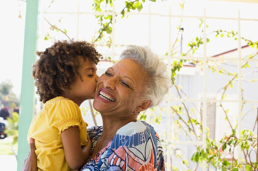 child kissing grandmothers cheek